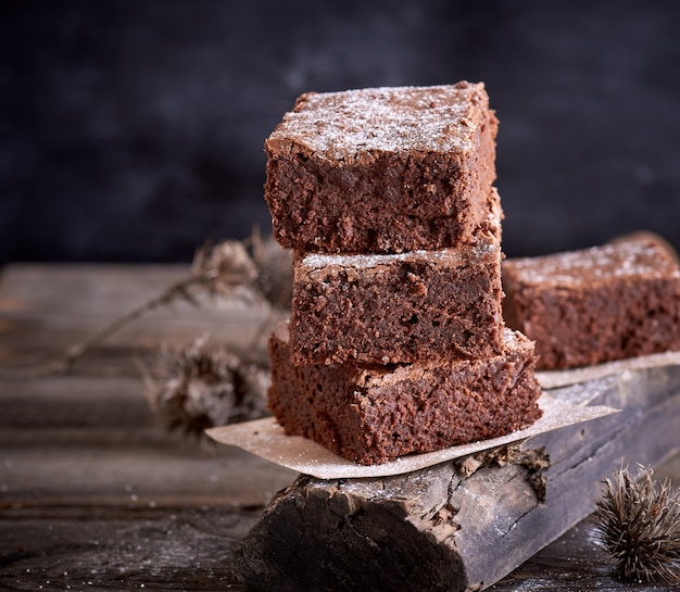 Stos kwadratowych kawałków pieczonego ciasta brownie brązowy
