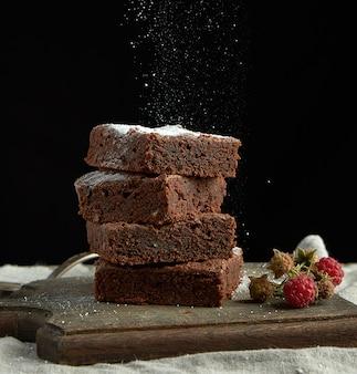 Stos kwadratowych pieczonych ciastek czekoladowych brownie posypanych białym cukrem