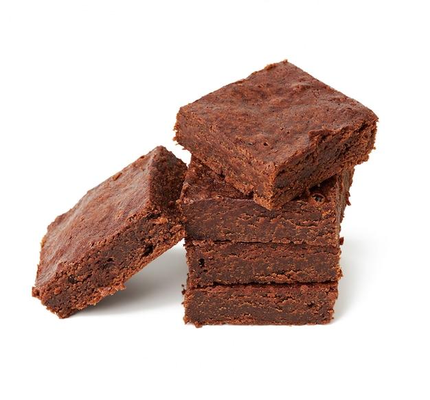 Stos kwadratowych pieczonych kawałków ciasta czekoladowego brownie na białym tle na biały, pyszny deser, widok z góry