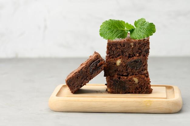 Stos kwadratowych pieczonych kawałków ciasta czekoladowego brownie na desce, pyszny deser, z bliska