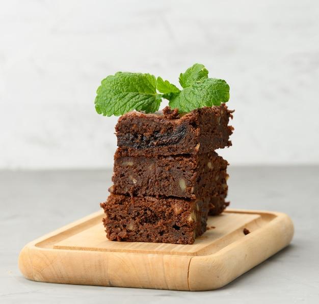 Stos kwadratowych pieczonych kawałków ciasta czekoladowego brownie na drewnianej desce, pyszny deser