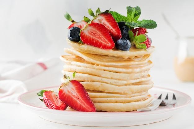 Stos małych naleśników na śniadanie z truskawkami, jagodami i słodkim sosem na lekkim stole. selektywna ostrość.