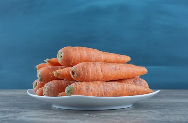Stos marchewek na talerzu na marmurowym stole.