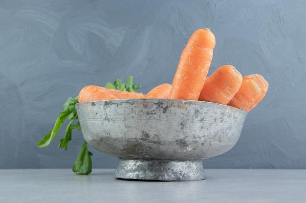 Stos marchewek w misce, na marmurowym tle.