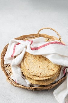 Stos meksykańskie tortille kukurydziane w wiklinowej tacy pokrytej ręcznikiem kuchennym