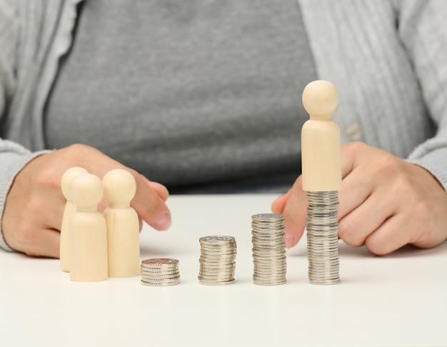Stos metalowych monet i drewniane figurki mężczyzn na białym stole. oszczędności i wydatki, budżet rodzinny, dotacje od państwa