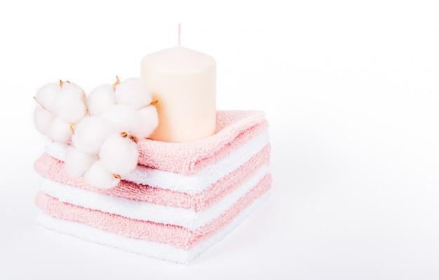 Stos miękkich ręczników, świec i bawełnianych kwiatów