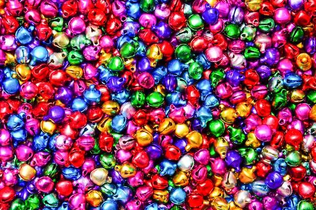 Stos mieszanych małych kolorowych dzwonów teksturowanej tło