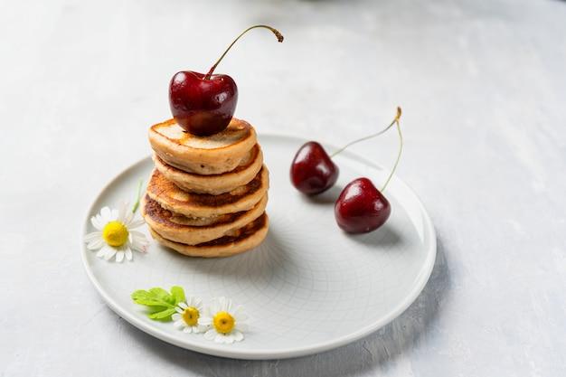 Stos mini naleśników, na talerzu z wiśniami