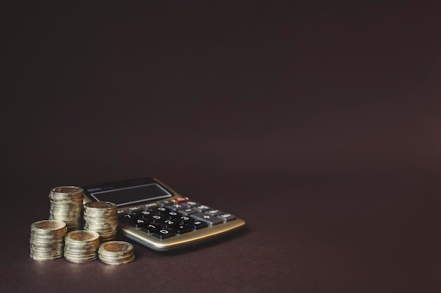 Stos monet i kalkulator. koncepcja oszczędzania pieniędzy, finansowych. oszczędność pieniędzy i dochodów pomysły inwestycyjne i zarządzanie finansami na przyszłość. skopiuj miejsce. koncepcja rozwoju biznesu. ryzyko finansowe.