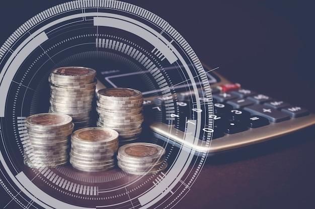 Stos monet i kalkulator z docelowym gologramem. koncepcja oszczędzania pieniędzy i zarządzania finansami
