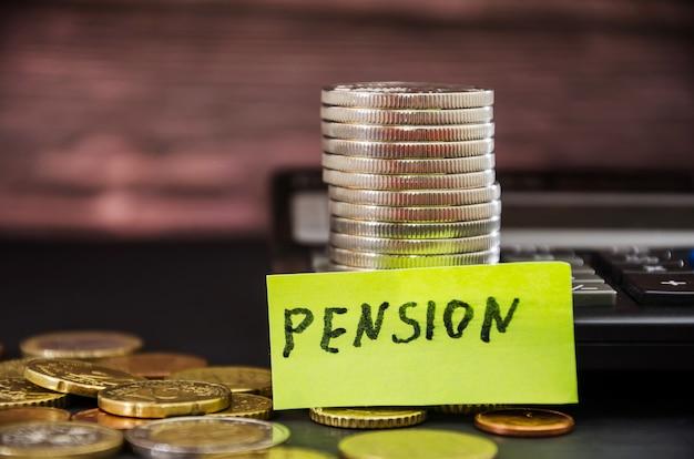 """Stos monet i napis """"pensja"""" na naklejce koncepcja oszczędności"""