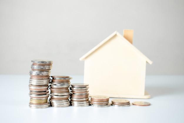 Stos monet i plany domów. inwestycje w nieruchomości i hipotekę finansową.