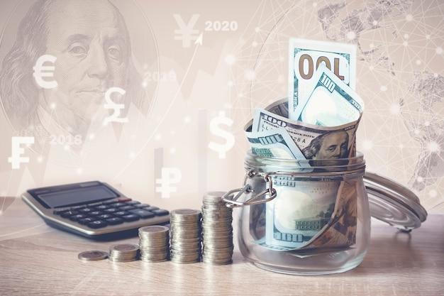 Stos monet, kalkulator, banknoty dolarowe w szklanym słoju, wirtualny hologram, ziemia, statystyka, wykres, ikony walut różnych krajów. oszczędności pieniędzy, dochód pomysły inwestycyjne, zarządzanie. koncepcja wzrostu biznesu.
