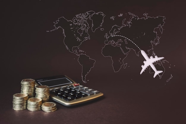 Stos monet, kalkulator, wirtualna mapa świata z hologramem i samolot. koncepcja oszczędzania pieniędzy, finansowych, podróży. oszczędność pieniędzy, dochodów pomysły inwestycyjne, zarządzanie. koncepcja rozwoju biznesu.