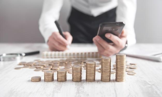 Stos monet na biurku. biznesmen za pomocą smartfona i pisania na notatniku