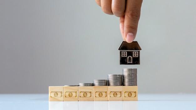 Stos monet na drewnianym bloku z ikoną pieniędzy i domową mobilną koncepcją finansowania i inwestycji o firmie zajmującej się nieruchomościami.