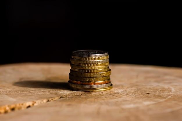 Stos monet na starym drewnianym stole z ciemnym tłem