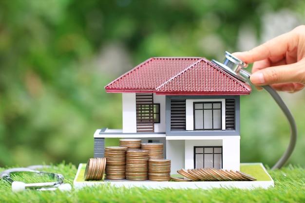 Stos monet pieniądze i businesswoman za pomocą stetoskopu, aby sprawdzić model domu
