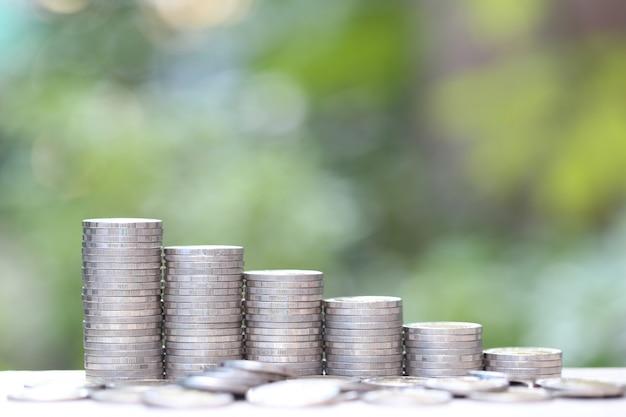 Stos monet pieniędzy na naturalnej zieleni, koncepcja inwestycji biznesowych