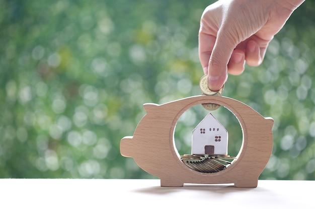 Stos monet pieniędzy w drewno skarbonka i model domu na naturalnym zielonym tle, inwestycje biznesowe i koncepcja nieruchomości