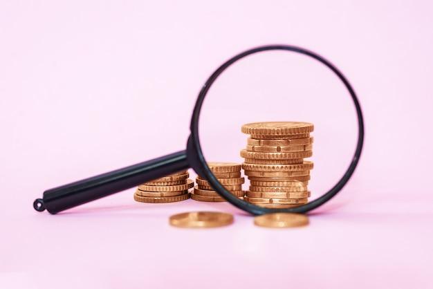 Stos monet przez lupę na różowym tle. monety euro.