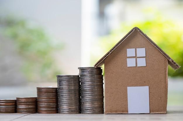 Stos monet rośnie, a model domu papierowego z zielenią rozmazuje tło dla oszczędności