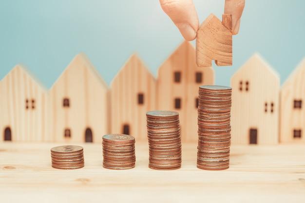 Stos monet z drewnianym modelem domu do oszczędzania pieniędzy na zakup nowej koncepcji domu.