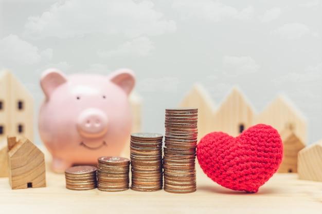 Stos monet z drewnianym modelem domu i skarbonką do oszczędzania pieniędzy na zakup nowego domu z koncepcją miłości serca.