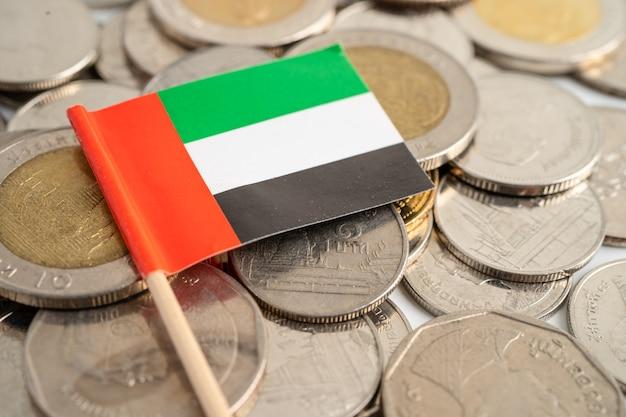 Stos monet z flagą emiratów arabskich na białym tle. flaga na białym tle.