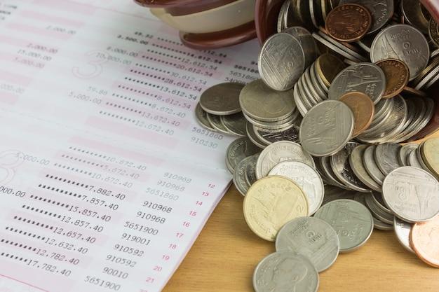 Stos monet z książeczką oszczędnościową