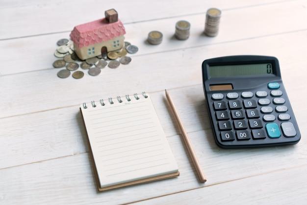 Stos monet z modelu domu i notebooka dla miejsca kopiowania i kalkulatora, plany oszczędnościowe dla mieszkaniowej koncepcji finansowej