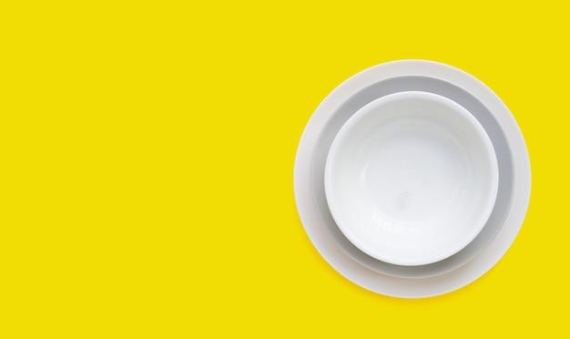 Stos naczyń na żółtym tle.