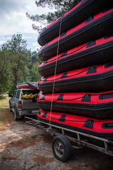Stos nadmuchiwanych łodzi raftingowych w pobliżu samochodu