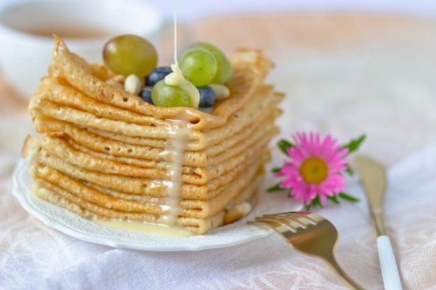 Stos naleśników z winogronami polanymi skondensowanym mlekiem na filiżankę herbaty