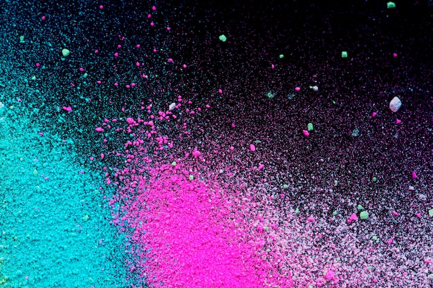 Stos naturalnego barwnego proszku pigmentowego. rozpryskiwają się cząsteczki zielonego różowego białego proszku