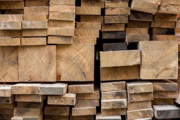 Stos naturalnych brązowych nierównych szorstkich desek o różnych rozmiarach, widok przekroju. drewno przemysłowe do stolarki, budownictwa, naprawy i mebli, materiały drzewne do budowy.