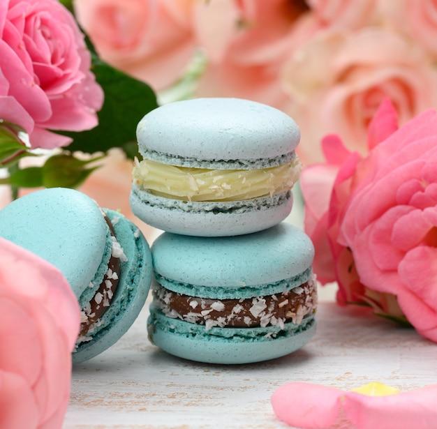 Stos niebieskich makaroników na białym stole i różowe pąki róż, pyszny deser, zbliżenie
