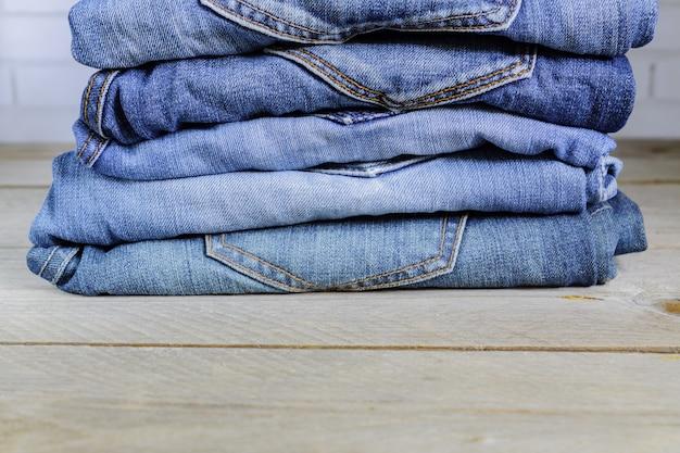 Stos niebieskie dżinsy na drewnianej półce. koncepcja odzieży uroda i moda