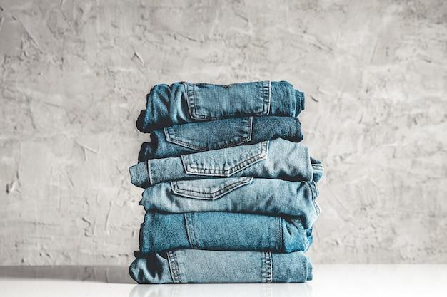 Stos niebieskie dżinsy na szarym tle