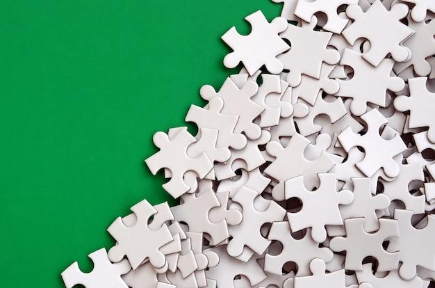 Stos niezłożonych elementów białej układanki leży na tle zielonej powierzchni.
