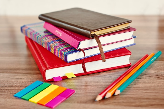 Stos notesów z ołówkami i kolorowymi zakładkami na drewnianym stole