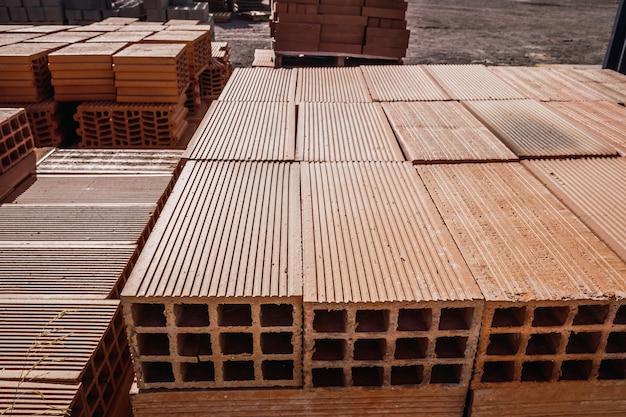 Stos nowych cegieł ułożonych w stos do budowy ściany w sklepie z materiałami budowlanymi.