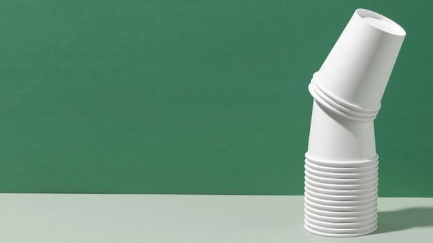 Stos nowych kubków kopiuje zielone tło przestrzeni