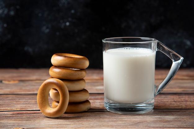 Stos okrągłych ciastek i szklankę mleka na drewnianym stole.