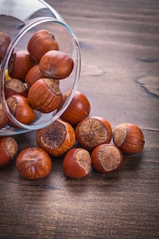 Stos orzechów laskowych w szklanej misce na vintage drewniana deska jedzenie