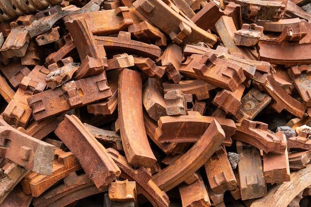 Stos ośniedziały stalowy hamulcowy ochraniacz lokomotywa w starym zaniechanym jardzie taborowa część produkci fabryka, rocznika kolejowy przemysł