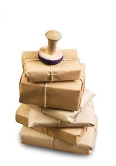 Stos paczek owinięty brązowym papierem pakowym na białym tle