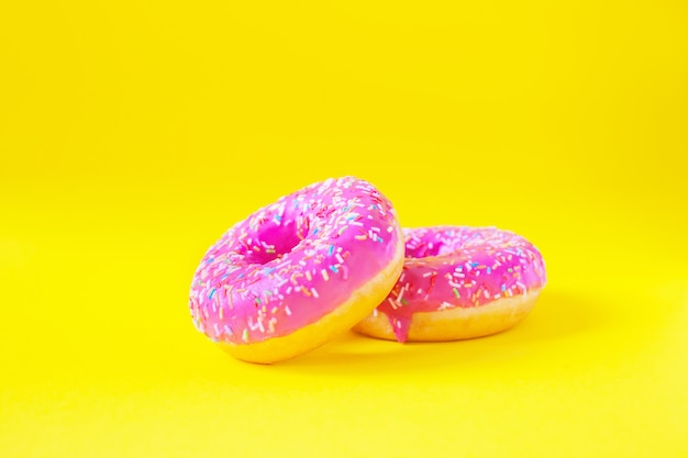 Stos pączki z różowym lukrem na żółtym tle widok z boku