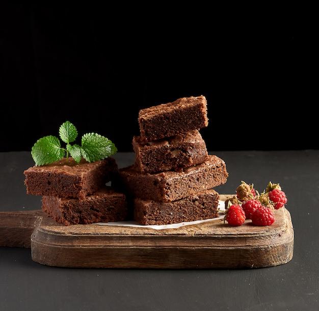 Stos pieczone kwadratowe kawałki ciasta brownie czekoladowe na brązowy deska do krojenia